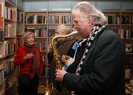 Jos Valster strooit aangename saxofoonklanken over de genodigden. Op de achtergrond Irene Smit in gesprek met Hendrik Vis.