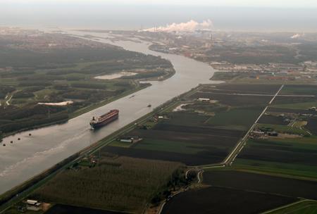 Een groen polderland doorsneden door 'breede rivieren' waar langs de randen rook uit hoge betonnen schoorstenen komt.