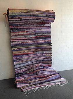 Met behulp van bewoners van dorpjes en vrijwilligers die kennis bezaten over de traditionele weeftechniek creëerde de Griekse kunstenares Fotini Gouseti een enorm tapijt dat bestaat uit tweeduizend zijden stropdassen. Foto: Prive