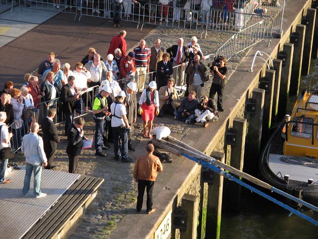 Wethouder Baljeu (midden in het rood en witte helm op) gooit de trossen los van het HAL-schip Rotterdam dat bij de cruiseterminal lag. Foto: Cees de Keijzer