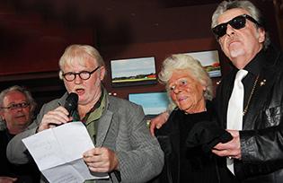 Blomsteel (himself, midden met moeder) tijdens de opening van een van zijn vele exposities in de stad (café Centraal) met (links) Tim Donia en (rechts) een als Hell's Angles verklede Jan Vleghaar met motorjack en zonnebril.